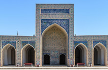 Madrasa Facade With A Tall Arch And Blue Ceramic Glazed Tiles, Decorated Walls And A Colonnade In Bukhara.