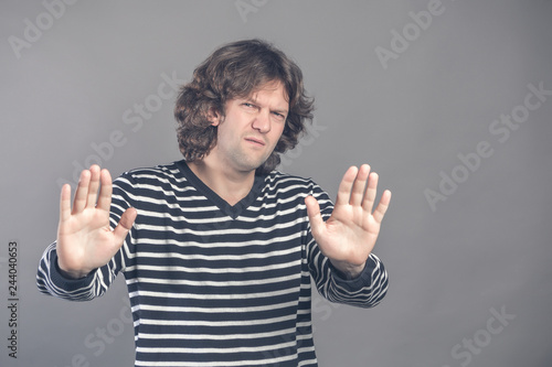 Fotografía  Attractive brunet male shows refusal gesture, curly man does not want to partici