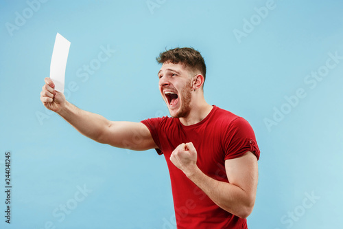 Leinwand Poster Young boy with a surprised happy expression bet slip on blue studio background