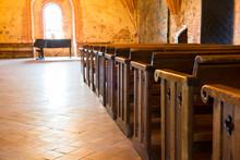 Row Of Empty Wooden Seats In Catholic Church