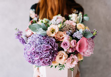 Very Nice Young Woman Holding Beautiful Blossoming Bouquet Of Fresh Hydrangea, Calla Lilies, Roses, Eustoma, Carnations, Eucalyptus, Mattiola Flowers In Purple Color On The Grey Wall Background