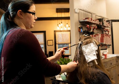 Millennial hair stylist applying highlights in a salon