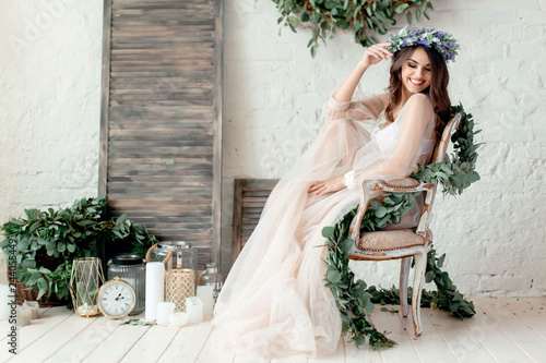 A girl in a beige peignoir, with a wreath of flowers on her head, poses in the s Fototapeta