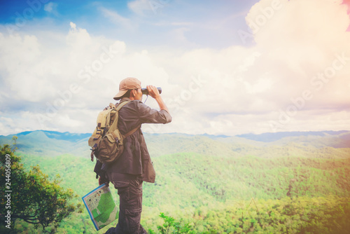 Young Man standing alone in forest outdoor with sunset nature on background Travel Lifestyle and survival concept Fotobehang