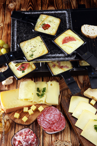 Delicious traditional Swiss melted raclette cheese served in individual skillets with salami.