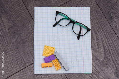 Fotografía  Eye glasses with notebook, constructor on wooden background