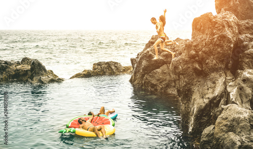 Fotografia  Young friends vacationers jumping on natural pool at travel beach location - Spo