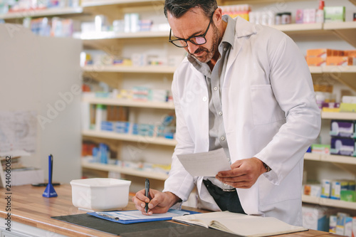 In de dag Apotheek Pharmacist writing prescription pharmacy counter