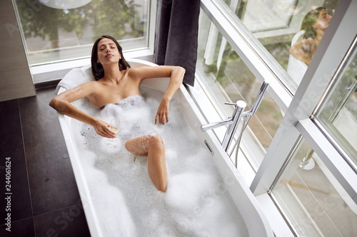 Attractive girl relaxing in bath with foam and drink champagne top view Canvas Print