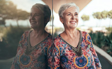 Portrait Of A Beautiful Grey Haired Middle Aged Woman Looking Out Into The Distance With Her Reflection