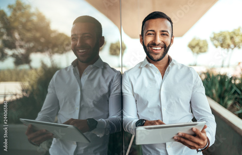 Obraz Indian businessman standing outside building with a tablet looking into camera - fototapety do salonu