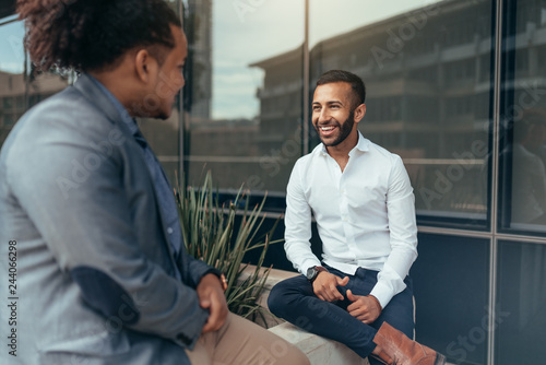 Two trendy businessmen talking and laughing casually outside