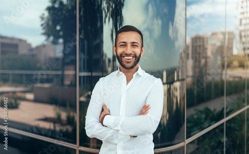 Fototapeta Portrait of a young confident smiling indian man with his arms crossed looking into the camera obraz