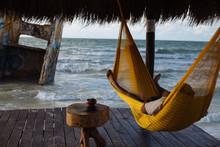 Man Relaxing In Hammock Near Sea