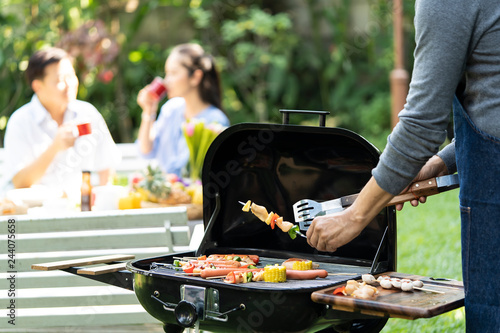 Asian men are cooking for group senior friends or family having  barbecue party in garden on summer. close up of hand cooking meat on barbecue for Asian couple dinner drinking alcohol and having,meal