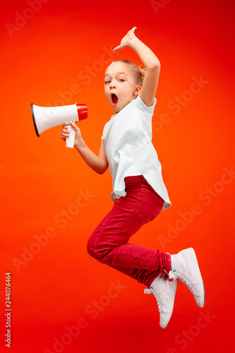 Beautiful young child teen girl jumping with megaphone isolated over red background Canvas Print