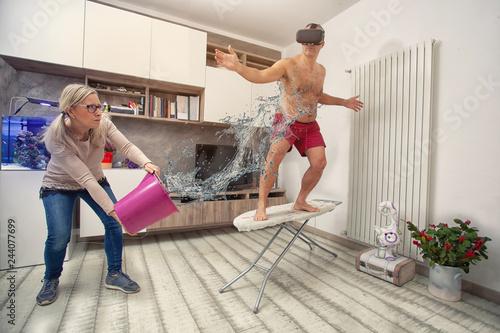 marito gioca a fare il surfer sull'asse da stiro e la moglie gli tira una secchi Canvas Print