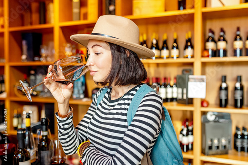 Fototapeta Happy asian Woman sniffing and tasting red wine in a glass in winery shop obraz