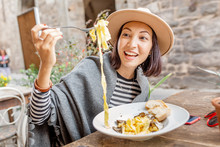 Happy Asian Woman Eating Pasta With Truffle In Outdoor Italian Restaurant
