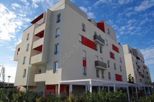 Photo  Bâtiment moderne blanc et rouge et ciel bleu dans un lotissement d'une ville de
