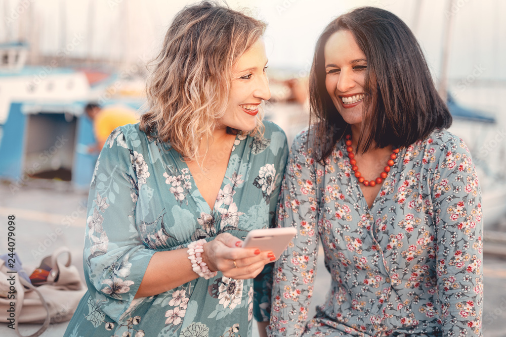 Fototapety, obrazy: Two women friends laughing while watching the smartphone screen