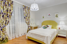 Interior Of Stylish And Sweet Bedroom For Girl In Green, White Colors And Big Window, Curtain In Floral Print. Comfortable And Cozy Bed, Pictures Over Bed And Dressing Table With Mirror Near.