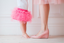 Mother's Legs And Daughters In Pink Skirts. My Daughter Is Trying To Put Her Legs To Her Mother. Legs Girls And Women. Mother Holds Daughter In Her Arms