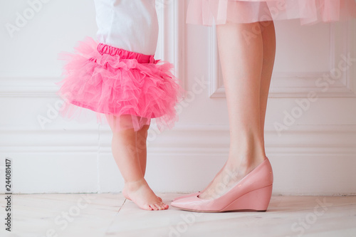 Fotografie, Obraz  Mother's legs and daughters in pink skirts