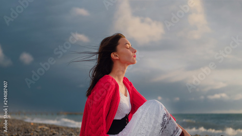 Fotografía  Sad brunette girl in red cardigan alone on empty seashore in cloudy weather
