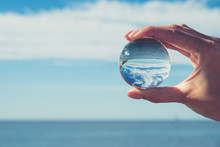 Woman's Hand Holding A Crystal Ball, Looking Through To The Ocean And Sky. Creative Photography, Crystal Ball Refraction
