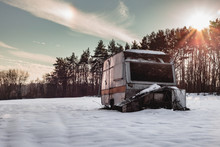 Beautiful Photo Of Old And Abandoned Caravan In The Middle Of Snow Covered Meadow In Winter Time. Illuminated Caravan (campervan) - Out Of Season At Sunset.