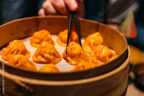 A hand is pinching Orange color Foie Gras Xiao Long Bao (Chinese Soup Dumpling) with chopsticks from bamboo streamer.