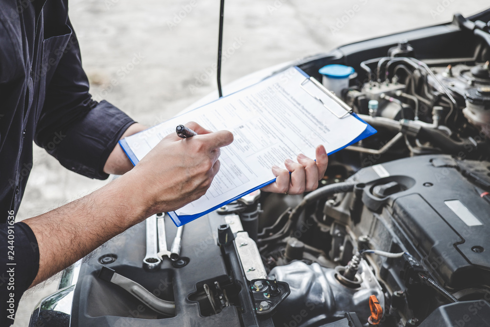 Fototapeta Services car engine machine concept, Automobile mechanic repairman checking a car engine with inspecting writing to the clipboard the checklist for repair machine, car service and maintenance