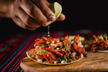 Close-up Of A Lime Being Squeezed In A Mexican Taco, With Traditional Colorful Background