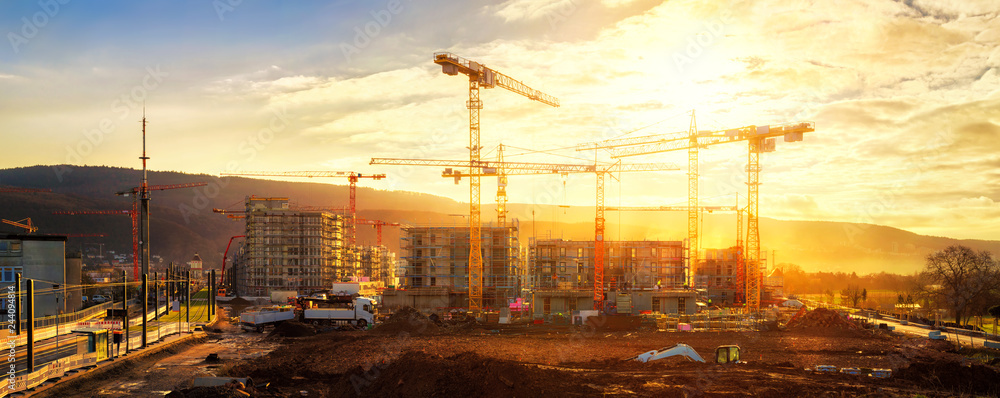 Fototapety, obrazy: Large construction site including several cranes, with lots of gold sunlight