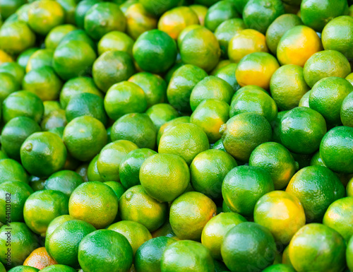 Close up fresh green mandarins in market. It can be used as a food background (selective focus)