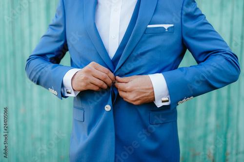 Fényképezés  the groom fastens his jacket