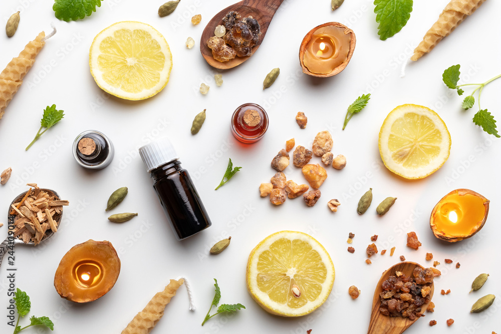 Fototapety, obrazy: Bottles of essential oil with frankincense, cardamon, melissa, fresh lemon and other ingredients