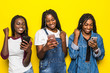 canvas print picture - Portrait of three happy young african woman friends smiling while using mobile phone together with win gesture isolated on yellow background