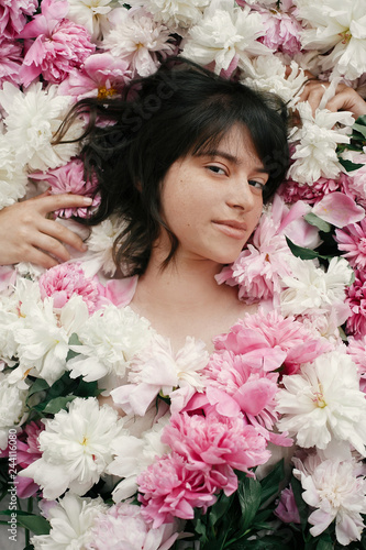 Fotografie, Obraz  Beautiful brunette girl lying in many pink and white peonies