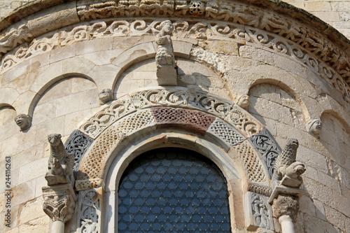 Photo arco di monofora con statue e decorazioni; abside della chiesa romanica di Ognis