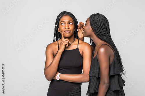 Photographie  Portrait of two happy young african women sharing secrets isolated on gray backg