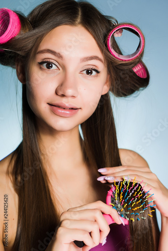 Fotografie, Obraz  attractive young girl makes a fashionable hairstyle with curlers and combs