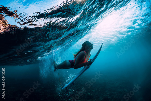 Photo  Attractive surfer woman dive underwater with under wave and sun light