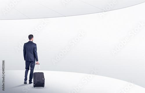 Businessman with back walking in a white waiting room with empty walls around Billede på lærred