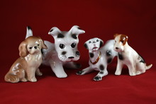 Four Porcelain Dogs  On A Red ...