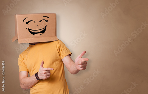 Young man with happy face illustrated cardboard box on his head Fotobehang