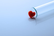 One Red Heart And A Medical Or Laboratory Glass Test Tube. Toned In Blue. Close-up. Copy Space.
