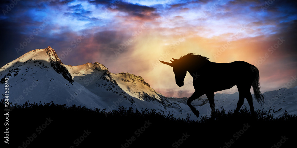 Unicorn silhouette at sunset with snowy mountains in the background