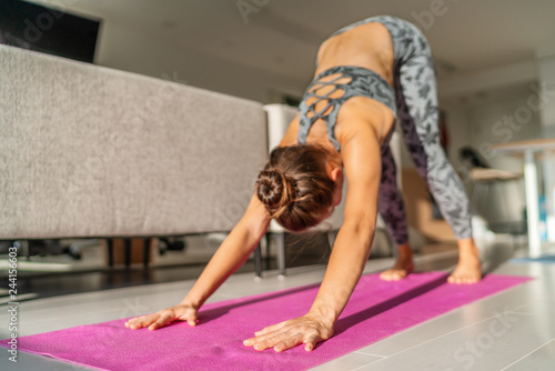 Slika na platnu Yoga morning woman stretching in downward dog pose in living room at home training indoors